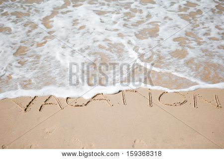 Vacation written on tropical beach white sand with wave