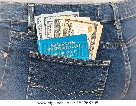 Kazakhstan passport and dollar bills in the back jeans pocket. Money for travel and shopping