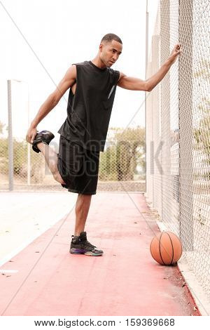 Photo of young african basketball player making sport exercises. Shooting at basket outdoor.