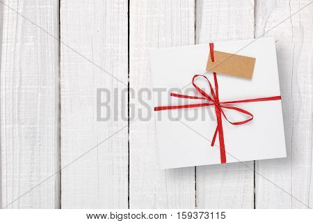 White gift box with tag on white wooden background