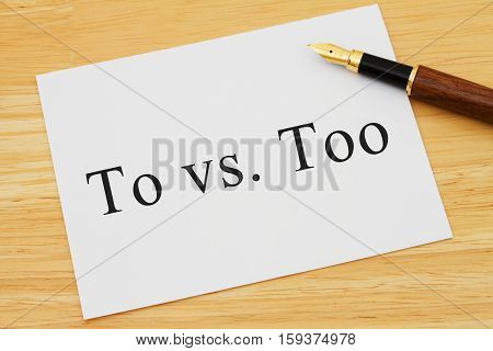 Learning to use proper grammar A white card on a desk with a pen with words To vs Too