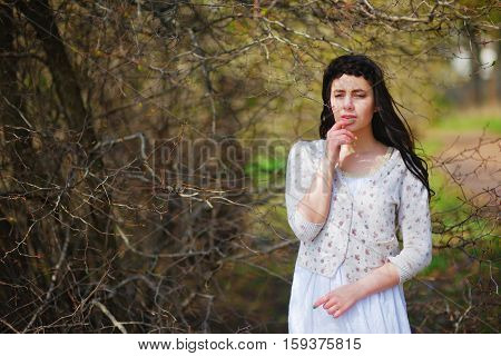 Gorgeous portrait of beautiful romantic girl brunette with long hair wearing light clothing in the Park amid blossoming branches closeup.