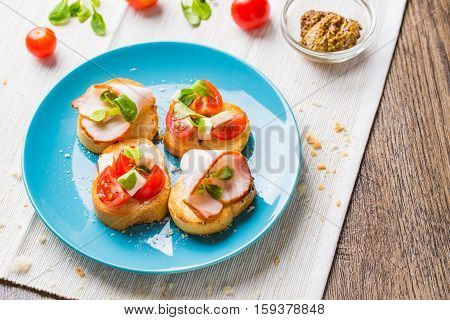 Traditional Italian antipasti bruschetta with tomato, cheese and bacon.