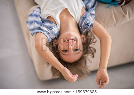 Cute kid at home upside down smiling