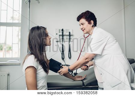 Physician measuring her patient's heart pressure and smiling to patient. Interacting and taking care of patient. Taking care of your health. Disease prevention.