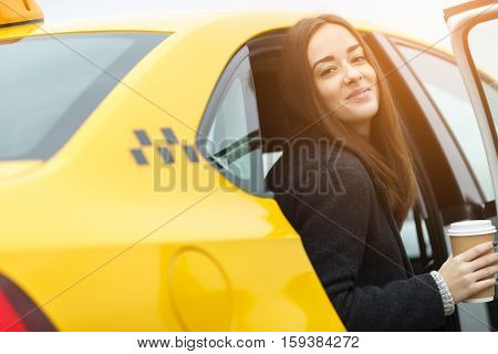 Cheerful woman with cup of coffee in hands sitting in yellow taxi with door open