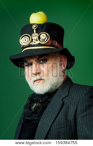 Frown senior bearded man or watchmaker with white beard in black hat with apple and watch mechanical metallic gears and cogwheels on green wall