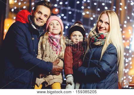 Cheerful family with kids against backdrop of night lights on winter evening