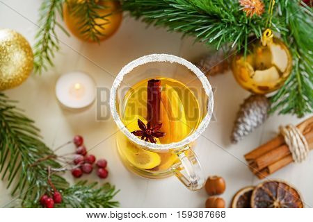 Glass of traditional hot drink on table by Christmas tree with decorations. Citrus tea. Top view.