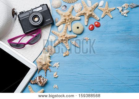 Straw hat sunglasses and photocamera among sea shells and stones on wooden surface