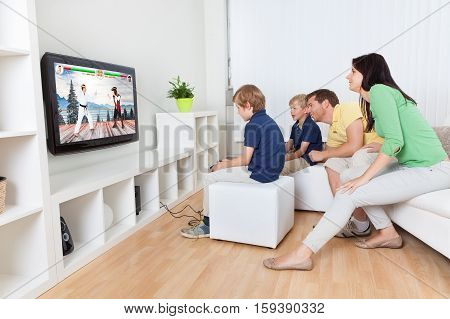 Happy Family Playing Fighting Game On Television At Living Room