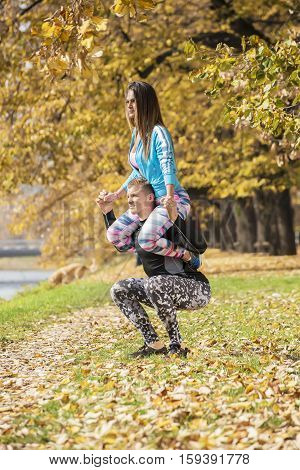 Beautiful Young Couple Doing Squats Together In The Park. Autumn Environment.