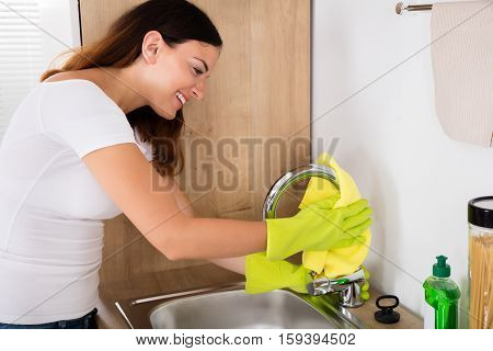 Young Happy Woman Cleaning The Steel Tap In The Kitchen