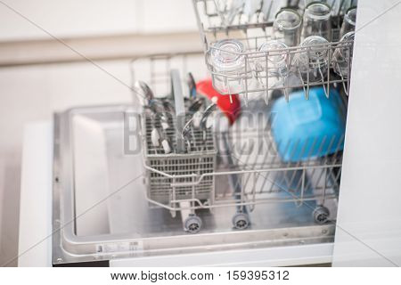 Open dishwasher with clean glass and dishes