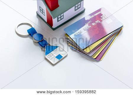 toy house, credit cards, key ring - concept mortgage on white background