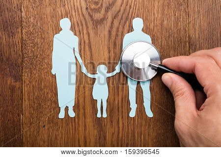 Person Holding Stethoscope On Family Papercut At Wooden Desk