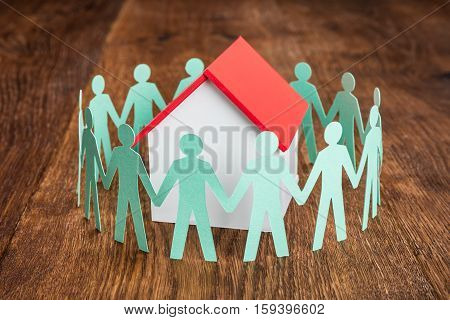 Papercut Surrounded By House Model On Wooden Desk