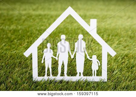 Close-up Of Papercut Of Family House On Grassy Field