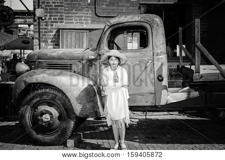 Toronto, Ontario, Canada, May 22, 2016, monochrome serious stylish beautiful little girl standing in front of old classic vintage retro truck at Toronto distillery historic district area