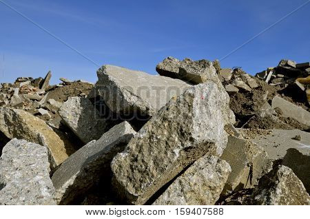 Huge broken segments of a concrete structure are dropped into a pile of debris