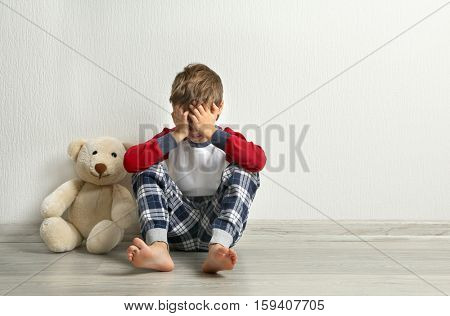 Crying little boy with teddy bear on floor in empty room