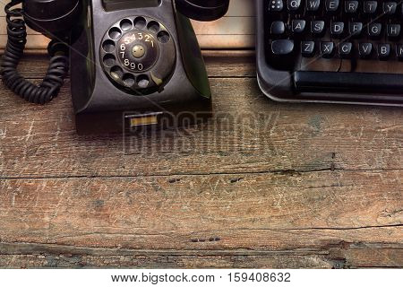 vintage black phone and typewriter on wooden table background