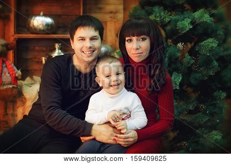 Portrait of a friendly and cheerful family Christmas mom dad and son looking at the camera smiling