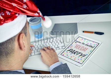 a young caucasian man with a santa hat sitting at his office desk looking to his tablet, where you can read the text christmas party you are invited
