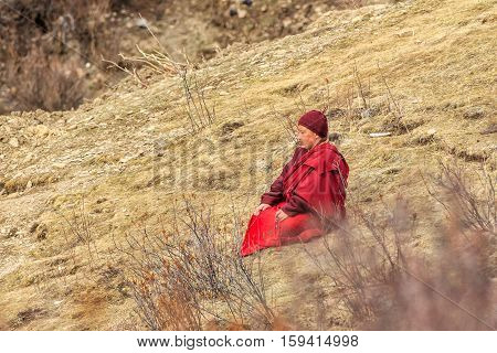 SICHUAN CHINA - MAY 3 2016: Monk sitting praying on grasses in the mountain at Larung Gar(Larung Buddhist Academy). a famous Lamasery in Seda Sichuan China.