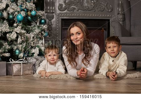 Happy family with  gift box are lying near Christmas tree at home. Merry Christmas and Happy New Year. Beautiful young mother with two sons.