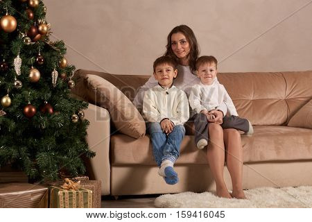 Happy family are sitting on a sofa near Christmas tree at home. Merry Christmas and Happy New Year. Beautiful young mother with two sons.