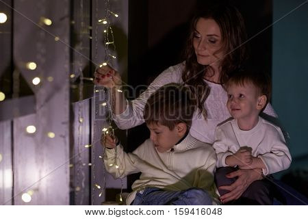 Happy family are sitting near window decorated Christmas garland at home. Christmas and New Year holiday. Beautiful young mother with two sons.