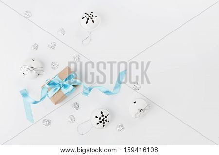 Christmas gift box with blue ribbon and jingle bell on white background from above. Holiday greeting card. Mockup. Flat lay composition.