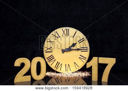 Christmas big golden watch with Latin numerals on a black luxury background. Numbers of new year 2017 gold color on glossy dark floor.