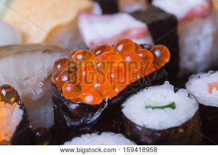 Sushi salmon roe macro shooting This is surrounded by Maki Sushi and pages. Focus salmon roe. Blurred background there are some points not in focus.