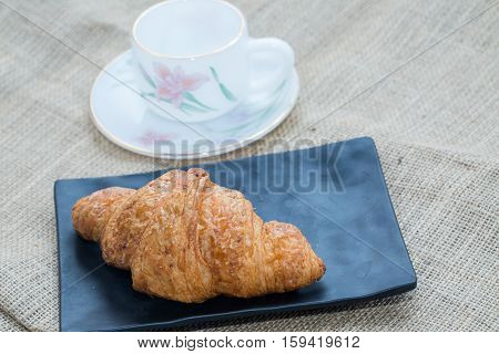 Croissant on a black plate. With a cup of tea. On a table covered with a cloth sack. Focus on Croissant. The background is blurred out of focus at some point.