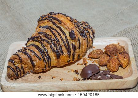 Closeup Croissants on a wooden plate chocolate and almonds. Focus on Croissant. The background is blurred out of focus at some point.