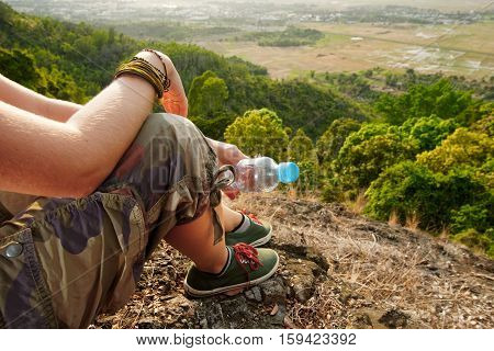 Portrait of hiker with a bottle of water sitting on top of the mountain and enjoying sunset. Travel Lifestyle concept mountains on background. Summer vacations