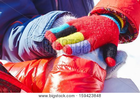 Children stacking their hands in winter, closeup