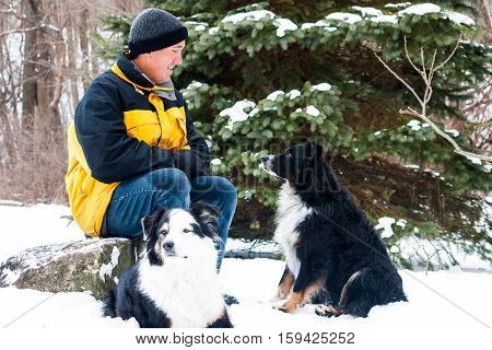 man sits to take a break while out for a walk with his dogs on a snowy winter day