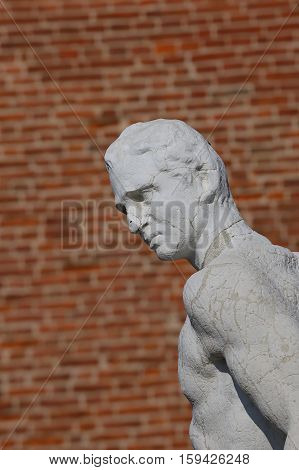 stone statue of a thinker character with the red brick background