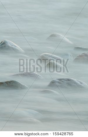 long exposure of sea and stones covered by water