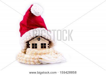House wooden wrapped in a scarf a cap of Santa Claus isolated on white. Conceptual image.