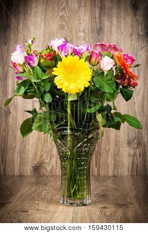 Mixed beautiful flowers in the vase on wooden background