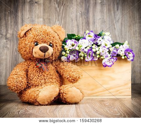 Bunch of flowers and a teddy bear on wooden background