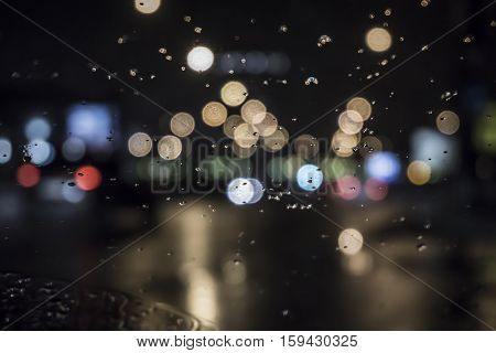Abstract background. Drops of water on the window. Wet the window with the background of the night city traffic view.