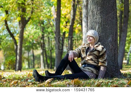 Beautiful young girl sits on a fallen autumn leaves in a park.