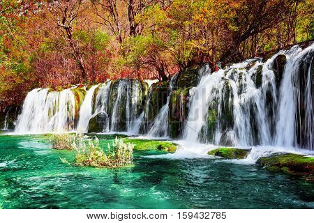 Waterfall And Azure Lake With Clear Water Among Fall Woods