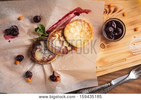 Cheese Pancakes With Cherry Sauce Served On Paper
