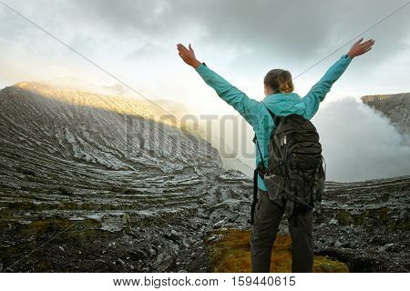 Traveler with backpack looking on top of a mountain volcano Ijen during sunrise. Island Java. Indonesia. Mountains landscape travel to Asia happiness emotion summer holiday concept